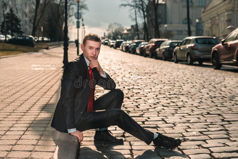 Stående av en brutal man i en svart dräkt och ett rött band En ung grabb sitter på gatan längs det gammalt stenar vägen arkivfoton