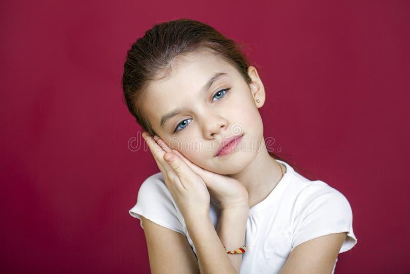 Stående av en charmig brunettliten flicka som ser kameran royaltyfri fotografi