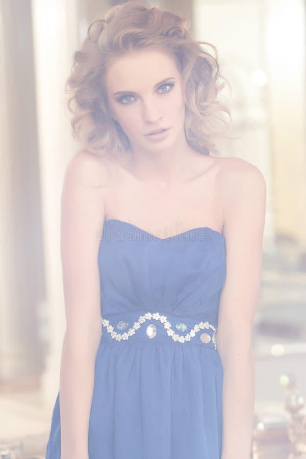 Stående av en charmig kvinna med den stilfulla lockiga frisyren som bär en blå klänning som poserar bredvid en spegel r royaltyfria foton