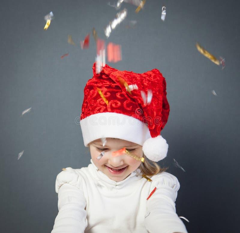 Stående av en charmig liten flicka i jultomten hatt fotografering för bildbyråer