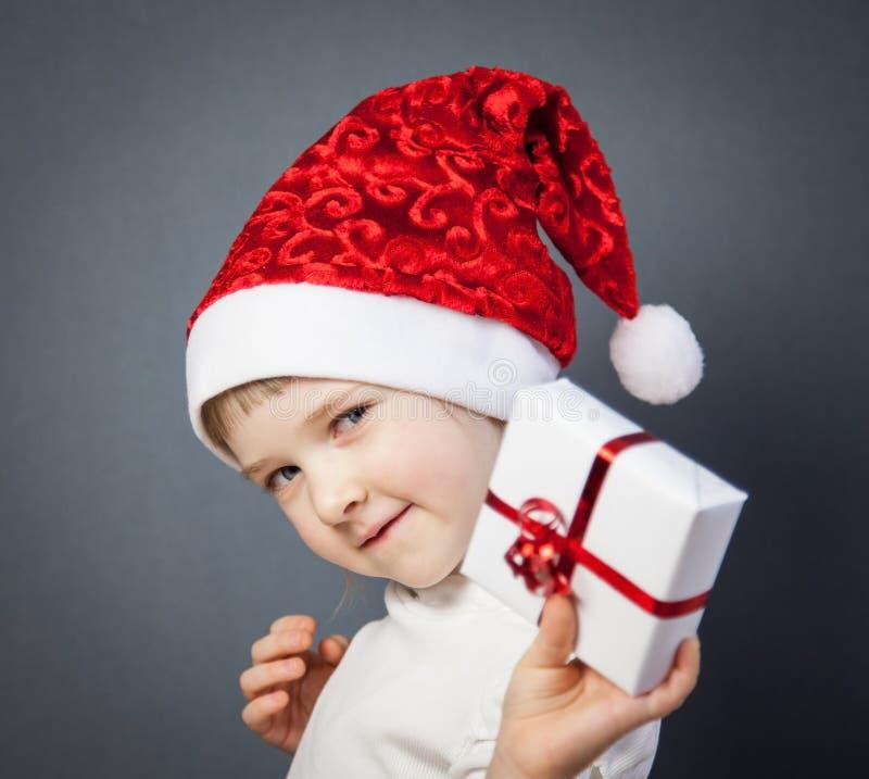 Stående av en charmig liten flicka i jultomten hatt arkivbilder