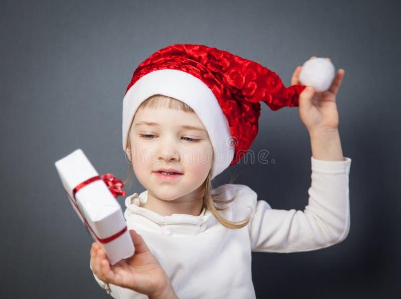 Stående av en charmig liten flicka i jultomten hatt royaltyfria bilder