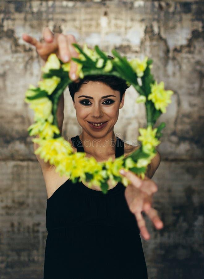 Stående av en charmig ung dam med en blommakrona, i en retro blus Flickan som pensively på ser på kameran fotografering för bildbyråer