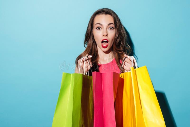 Stående av en chockad nätt flicka som rymmer färgrika shoppingpåsar royaltyfri bild
