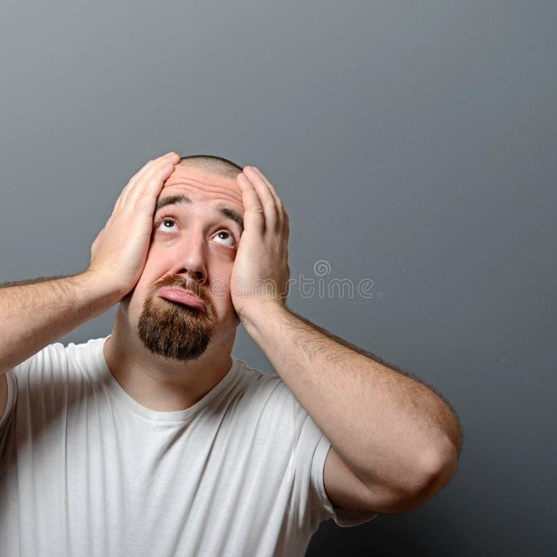 Stående av en desperat man i chock mot grå bakgrund arkivfoton