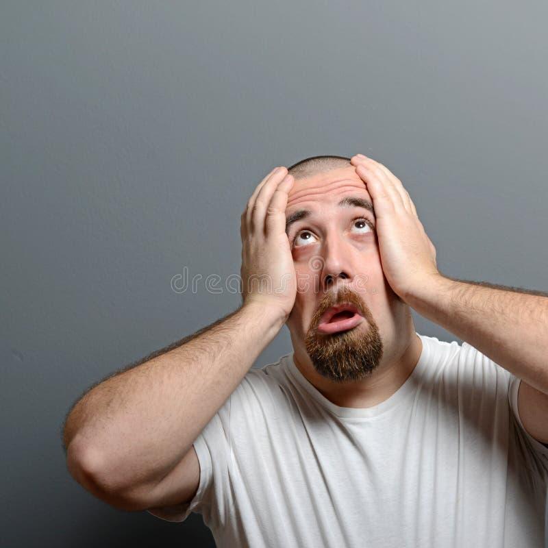 Stående av en desperat man i chock mot grå bakgrund arkivfoto