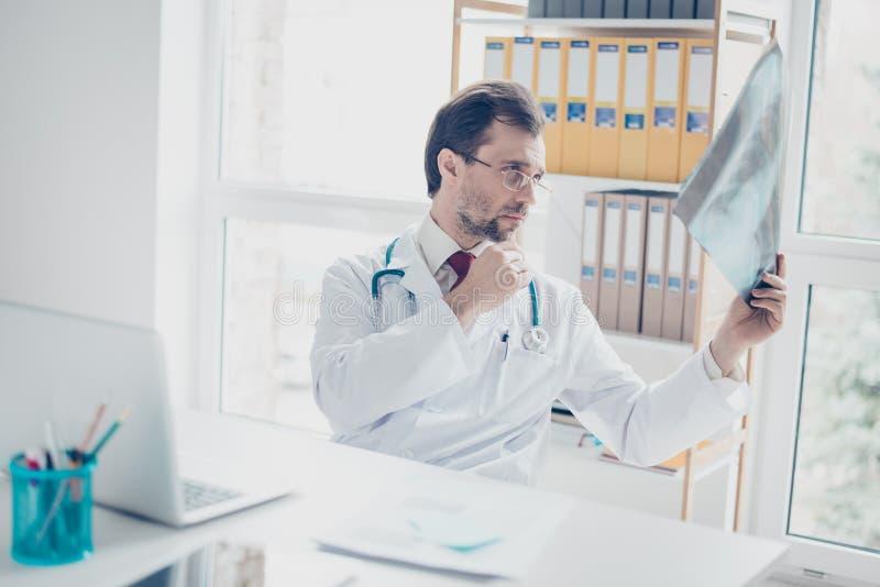 Stående av en doktor som ser en röntgenfotografering Han fokuseras, le royaltyfri bild