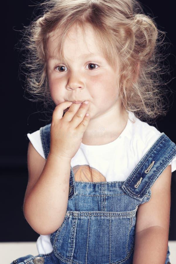 Stående av en eftertänksam gullig liten flicka i grov bomullstvilloveraller som sitter i en studio på svart bakgrund royaltyfri foto
