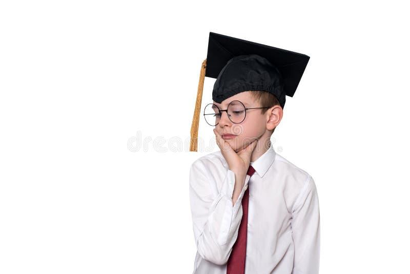 Stående av en eftertänksam pojke i en vit skjorta, exponeringsglas och ett akademiskt lock skola f?r copyspace f?r begrepp f?r sv arkivbilder