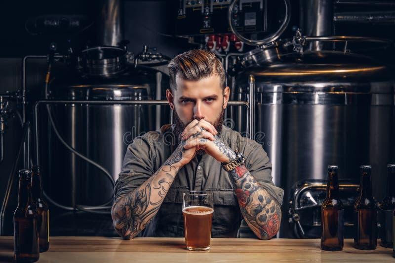 Stående av en eftertänksam tatuerad hipsterman med det stilfulla skägget och hår i skjortan i indie bryggeri arkivfoto