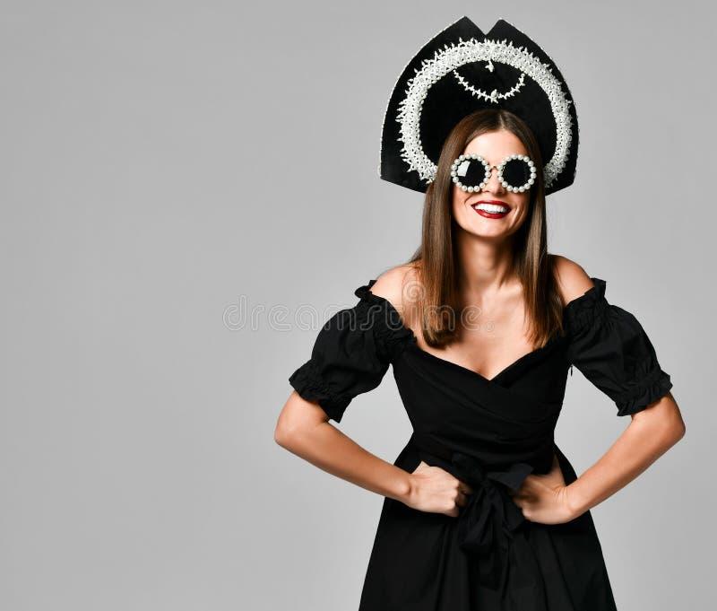 Stående av en elegant brunettsvartklänning, en svart solglasögon, ett kokoshniklock, ett långt hår och en härlig framsida arkivbild
