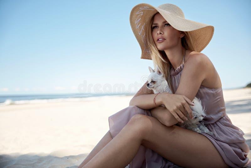 Stående av en elegant kvinna som kopplar av på en strand med hennes belove royaltyfria foton