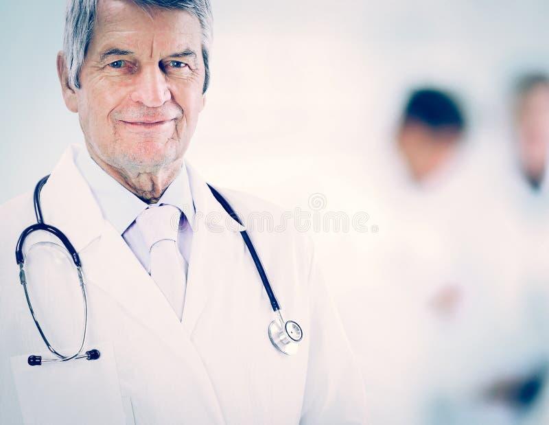 Stående av en erfaren läkare i ålder, i bakgrundsarbete fotografering för bildbyråer