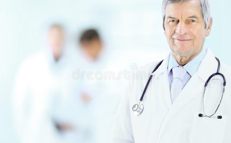 Stående av en erfaren läkare i ålder, i bakgrundsarbetslag royaltyfri fotografi