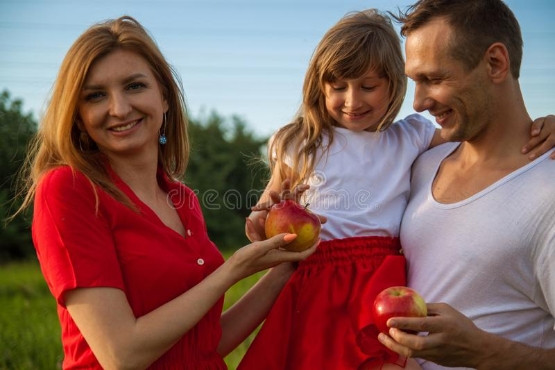 Stående av en europeisk familj av tre Den unga lyckliga småbarnsfamiljen i natur ler arkivbilder