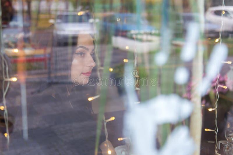Stående av en europeisk kvinna som sitter i kafét som ut ser fönstret Skjutit till och med fönstret royaltyfri bild
