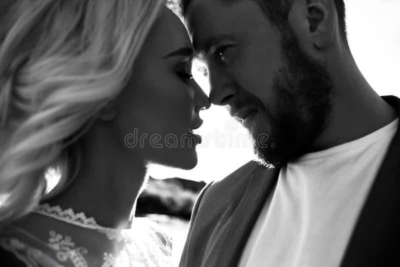 Stående av en förälskad närbild för par på en härlig solig dag på solnedgången Förälskelsesinnesrörelser och kramar i solen Blond royaltyfri foto
