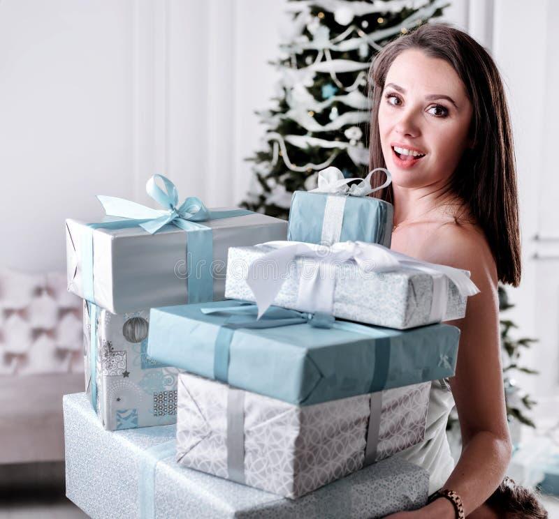 Stående av en förbluffad härlig dam som rymmer en grupp av gåvor arkivfoto