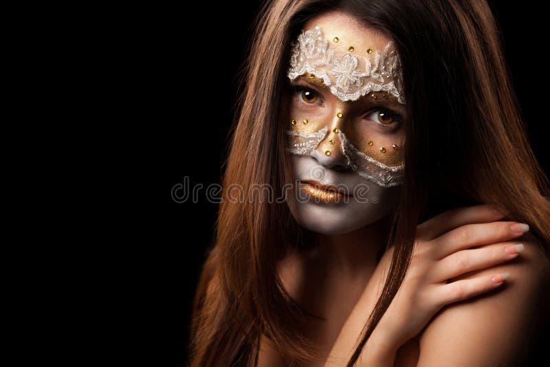 Stående av en försiktig kvinna med modesmink på svart backgro arkivbilder