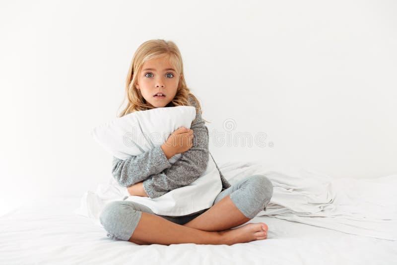 Stående av en förskräckt liten flicka som kramar kudden royaltyfria bilder