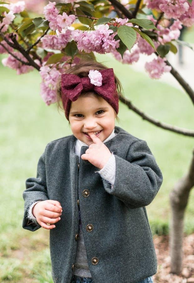 Stående av en förtjusande liten flicka med en pilbåge på hennes huvud i att parkera royaltyfri foto