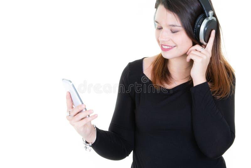 Stående av en förtjust ung kvinna som lyssnar till musik med telefonen och headphonen royaltyfria bilder