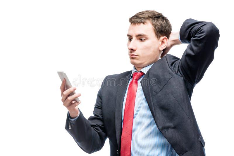 Stående av en förvånad affärsman med en telefon i hans hand royaltyfri fotografi