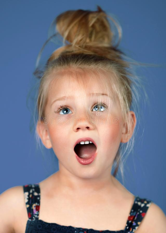 Stående av en förvånad flicka på en blå bakgrund royaltyfri bild