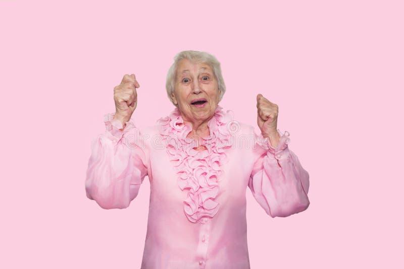 Stående av en förvånad hög kvinna över rosa bakgrund fotografering för bildbyråer