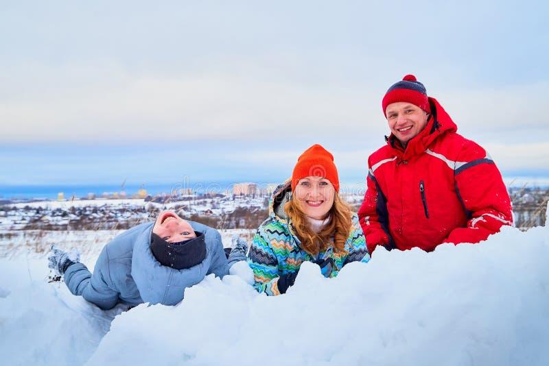Stående av en familj med fyra personer som har gyckel i snön royaltyfria bilder