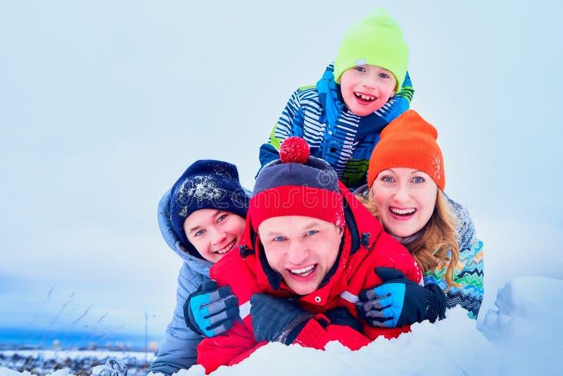 Stående av en familj med fyra personer som har gyckel i snön royaltyfri fotografi