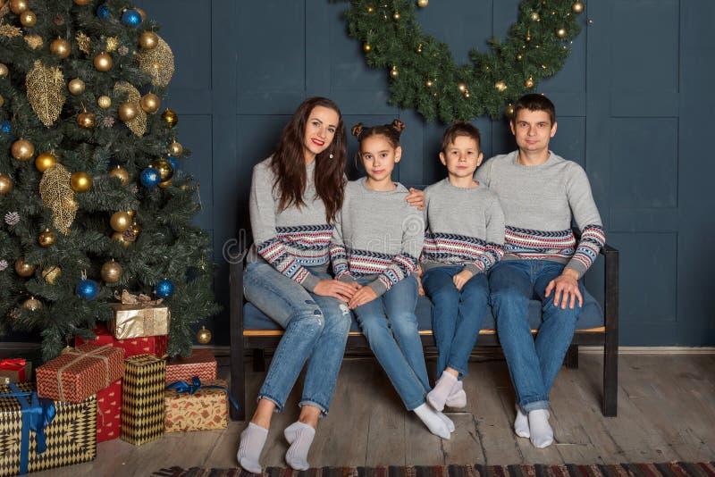 Stående av en familj med två barn i en familjblick som sitter på en soffa nära nytt års dekorerade julgran royaltyfri bild