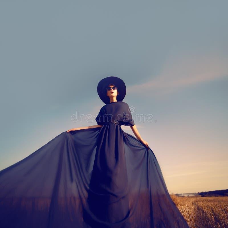 Stående av en flicka i en svart klänning i skogen arkivfoto