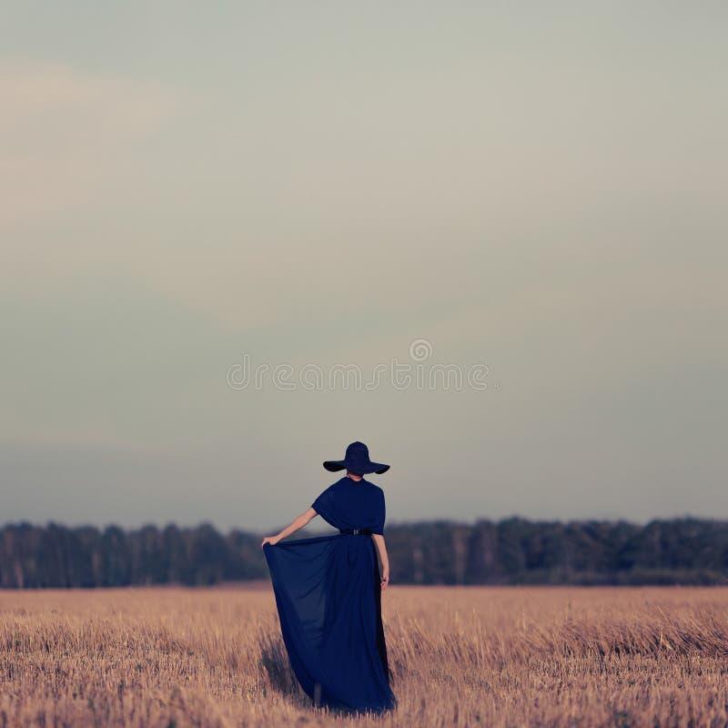 stående av en flicka i en svart klänning i skogen royaltyfri fotografi