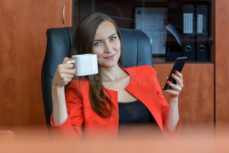 Stående av en flicka i ett rött sammanträde för affärsdräkt som vilar i en stol, dricker te och använder en smartphone avbrottsti arkivfoton
