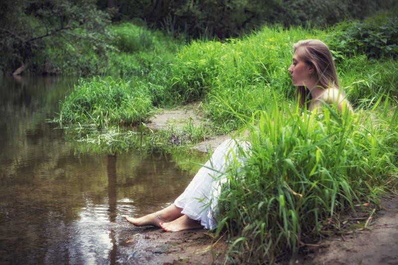 Stående av en flicka i ett vitt klänningsammanträde i gyttjan på flodbanken royaltyfri fotografi