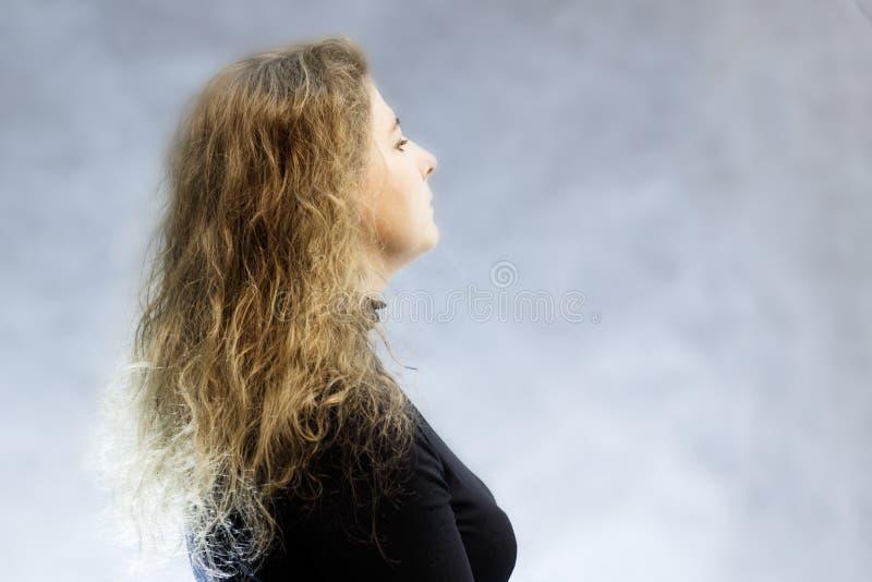 Stående av en flicka i en halsduk i ett svart omslag på en mörk bakgrund arkivfoton