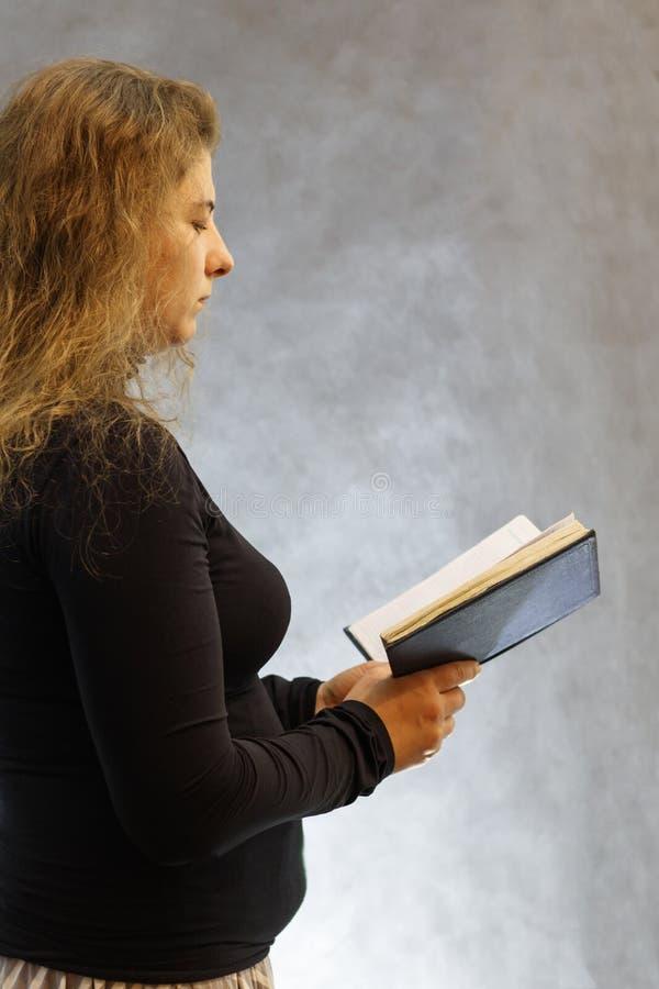 Stående av en flicka i en halsduk i ett svart omslag på en mörk bakgrund arkivbilder