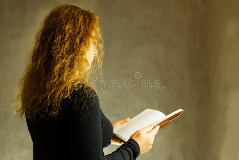 Stående av en flicka i en halsduk i ett svart omslag på en mörk bakgrund arkivfoto