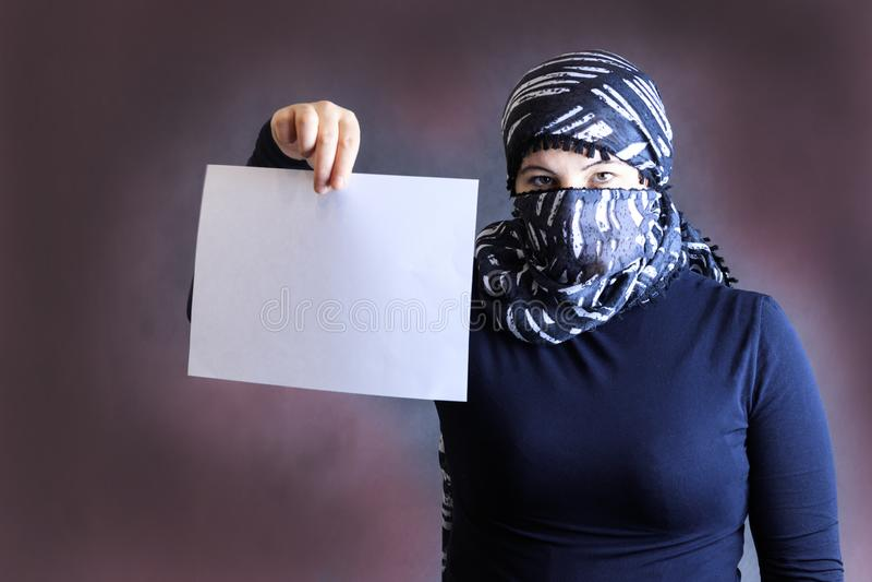 Stående av en flicka i en halsduk i ett svart omslag på en mörk bakgrund royaltyfri foto