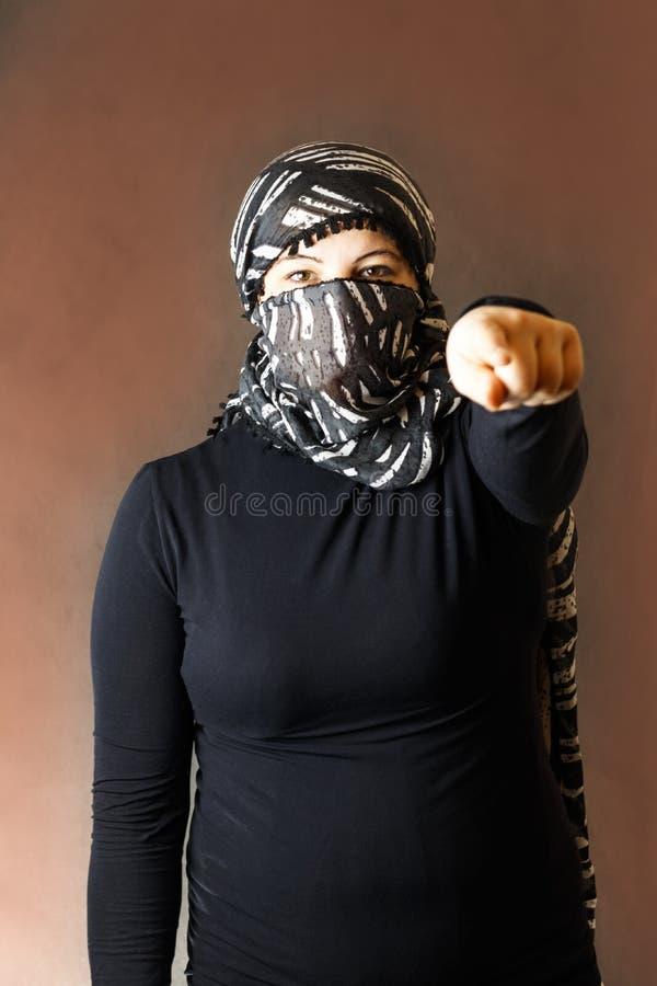 Stående av en flicka i en halsduk i ett svart omslag på en mörk bakgrund royaltyfri bild