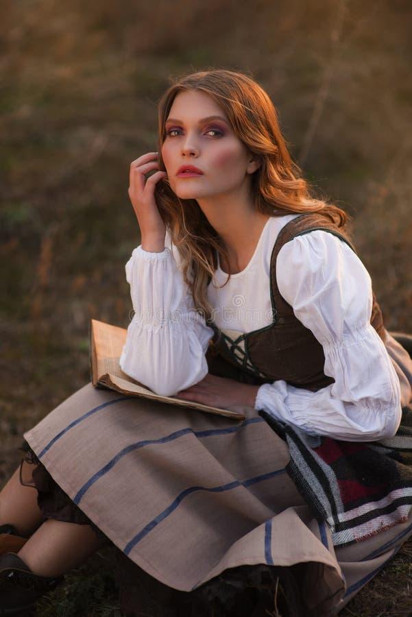 Stående av en flicka i en historisk klänning med en bok royaltyfri foto
