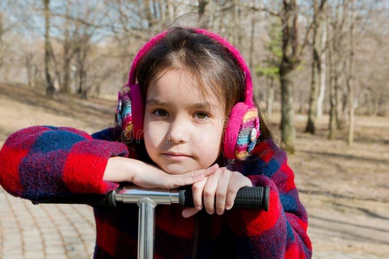 Stående av en flicka i varm hörlurar som lutar på hjulet av en sparkcykel arkivbild