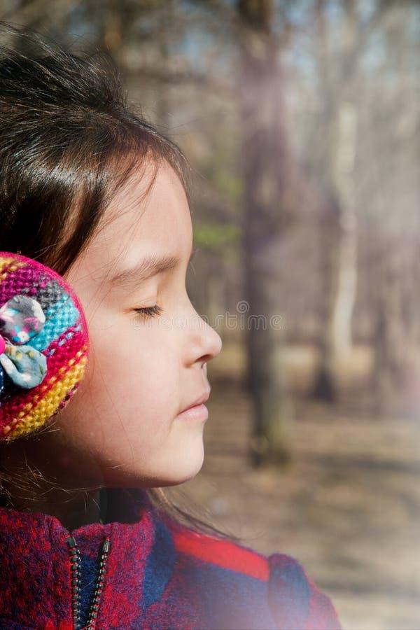 Stående av en flicka i varm hörlurar som täcker henne ögon i profil royaltyfria foton