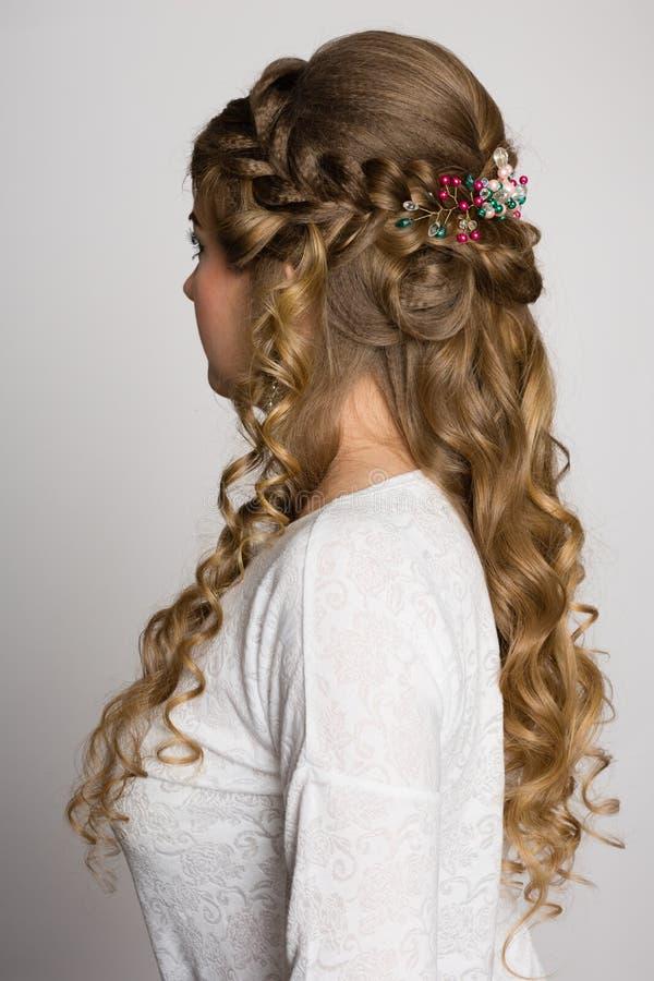 Stående av en flicka med en lång moderiktig frisyr från sidan arkivbild