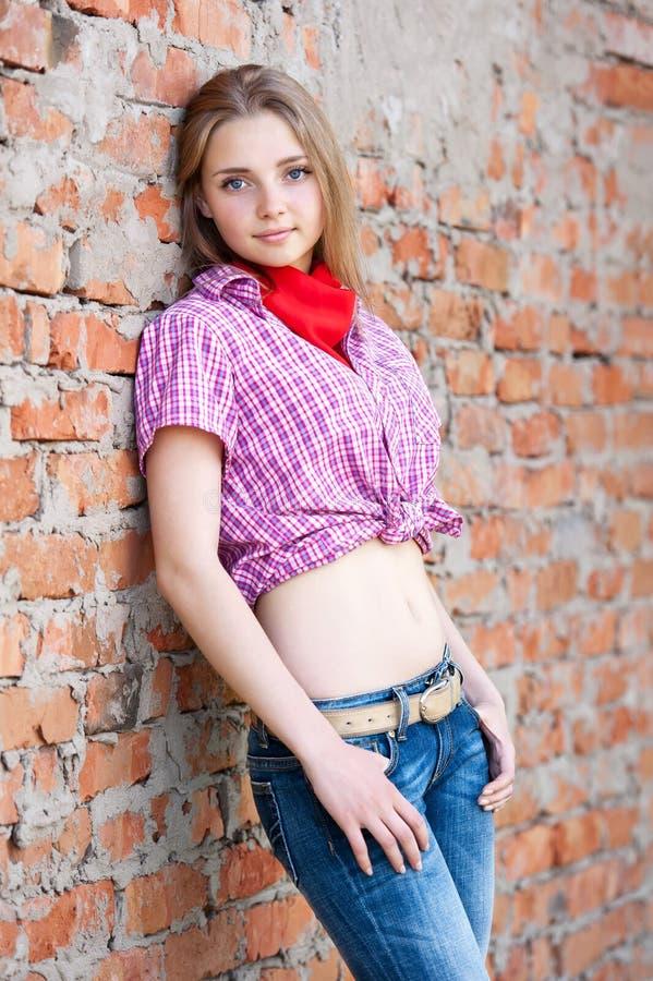 Stående av en flicka med en tegelstenvägg arkivfoto