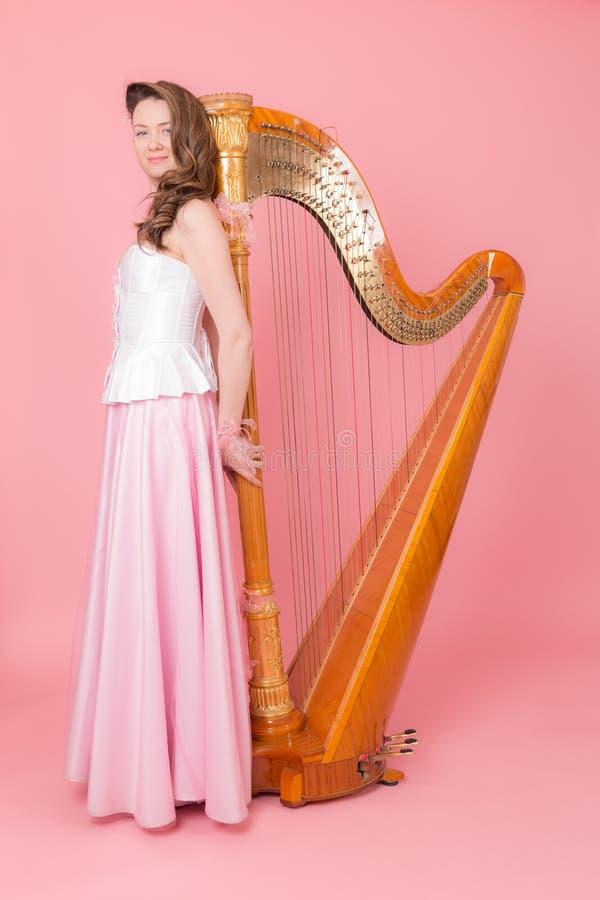 Stående av en flicka med en harpa royaltyfri bild