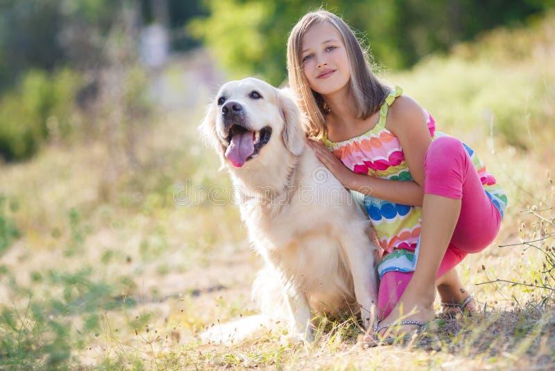 Stående av en flicka med hennes härliga hund utomhus royaltyfri bild