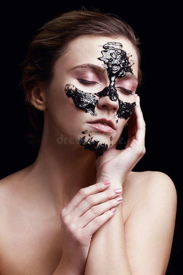 Stående av en flicka med en kosmetisk skönhetmaskering på hennes framsida på svart bakgrund royaltyfria foton