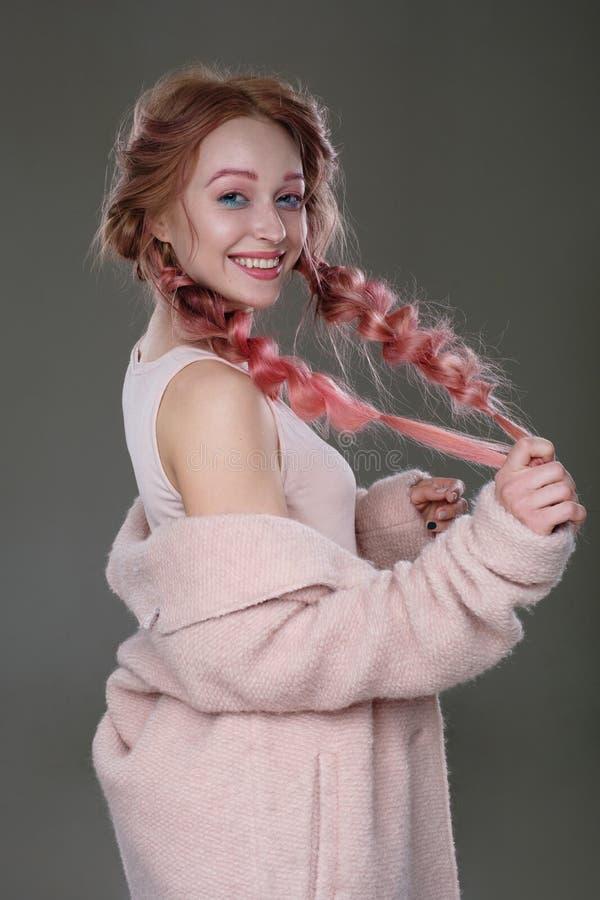 Stående av en flicka med rosa hår i flätade trådar med blå och rosa makeup, ett rosa lag som är slitet av skuldran som står i en  royaltyfri fotografi